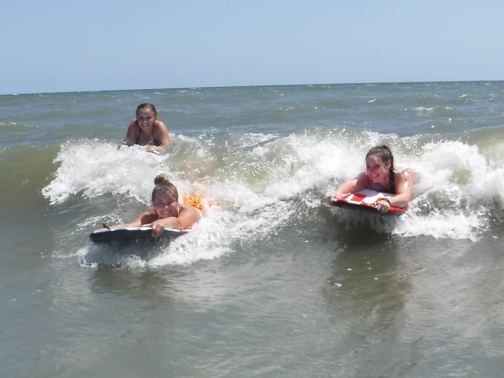 Friends riding the wave in on Holden Beach
