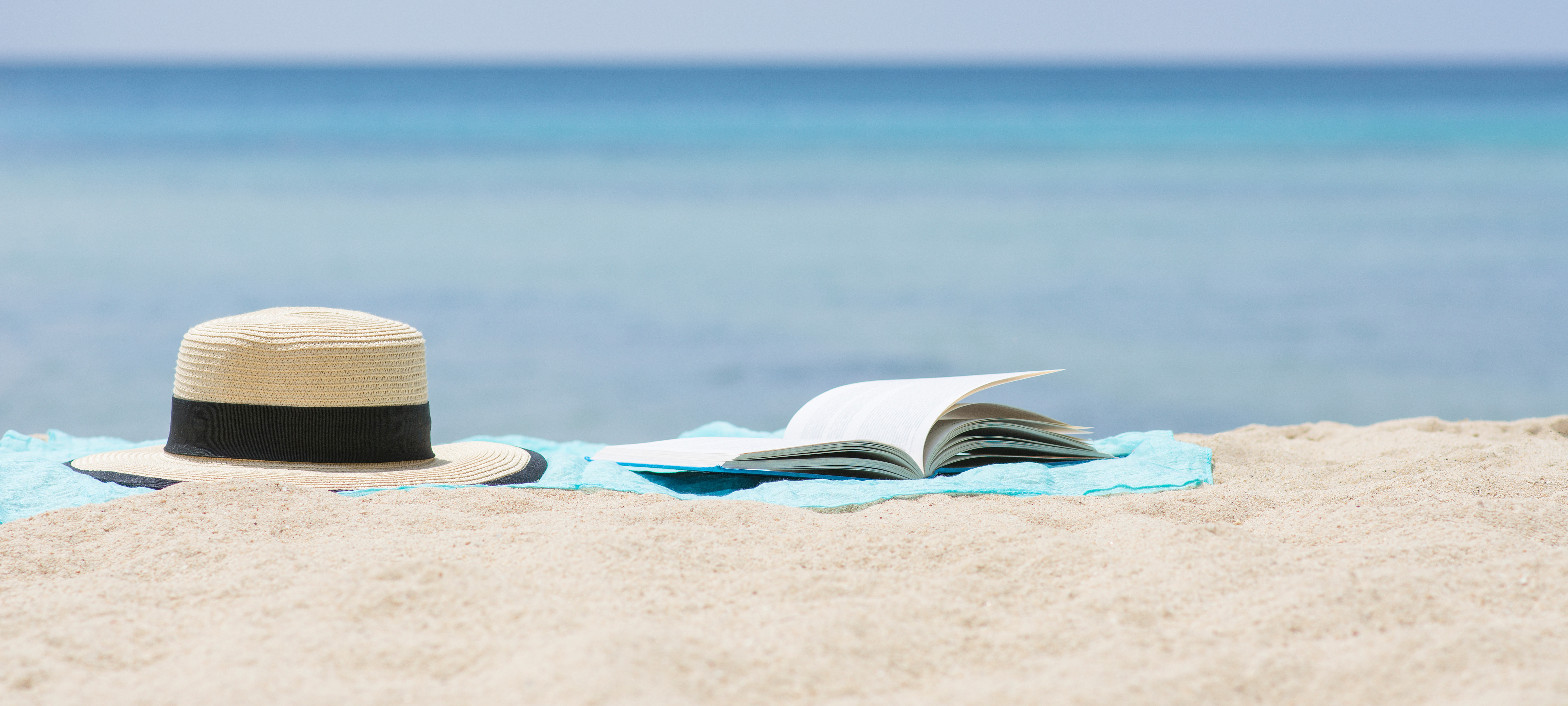 hat and open book on sandy beach