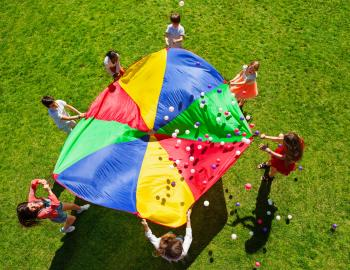 Kids Playing In Grass With Parachute