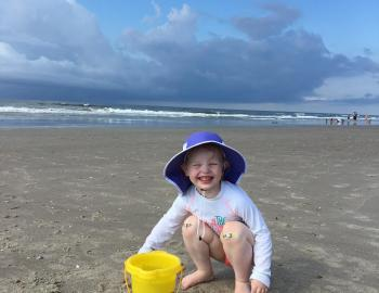 kid playing with beach bucket at holden beach