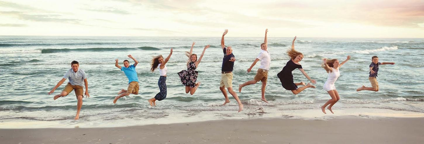 Hobbs Realty vacationers jumping up on Holden Beach