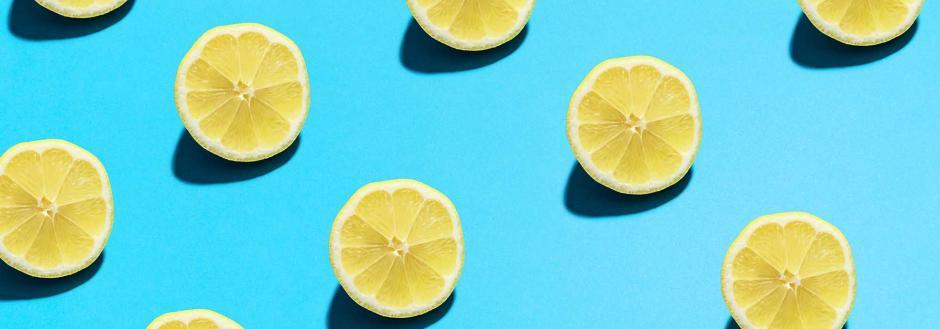 Fresh lemons cut in half on a bright blue background