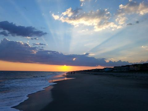 Sun peaking through the clouds at sunset on Holden Beach