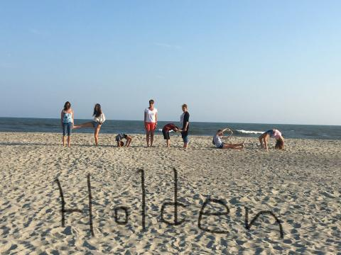 Kids spelling out Holden on the beach