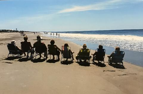 Family sitting is beach chairs on Holden Beach