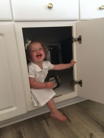 Little girl hiding in cabinet laughing