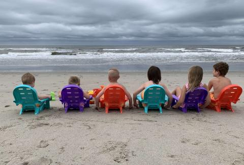 Kids lined up in beach chairs on the beach