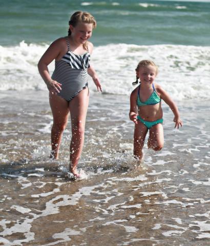 Two little girls running through waves on Holden Beach