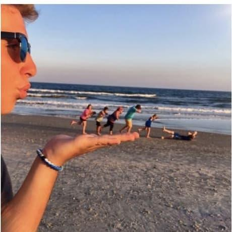 Young man pretending to blow people over on Hobbs beach