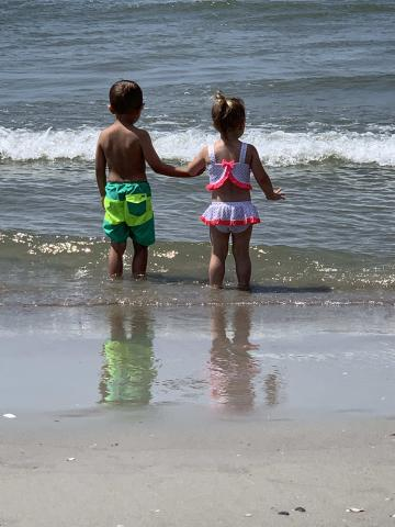 Brother and sister holding hands on the beach