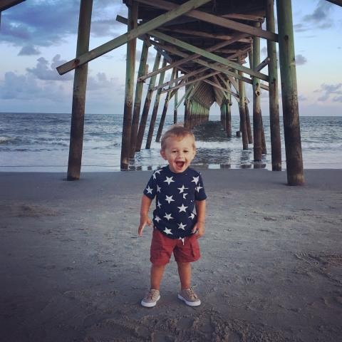 Little boy standing by the pier looking very surprised