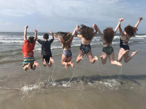 Kids jumping up while holding hands on Holden Beach