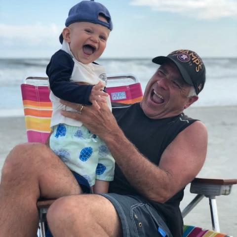 Grandpa holding his laughing grandson on the beach