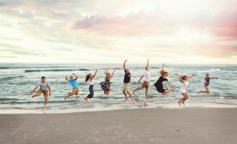 family jumping at holden beach