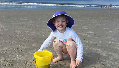 Girl smiling on Holden Beach with her bucket