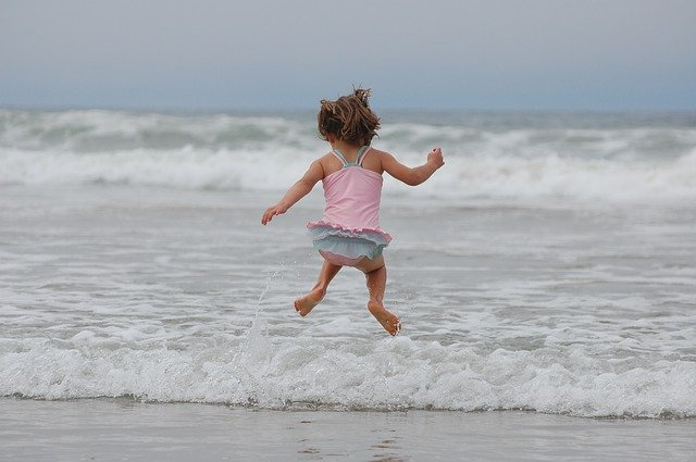 girl jumping waves on the beach