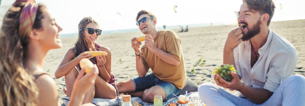 happy-group-of-people-eating-on-beach