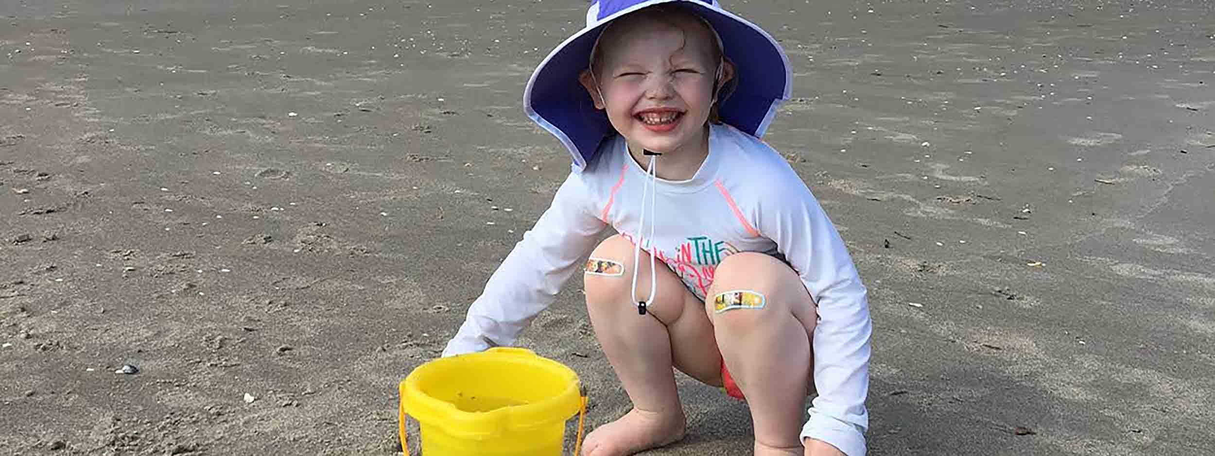 Little girl on the beach with a bucket of sand