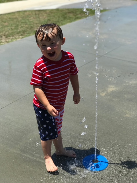 kid playing in holden beach splash pad
